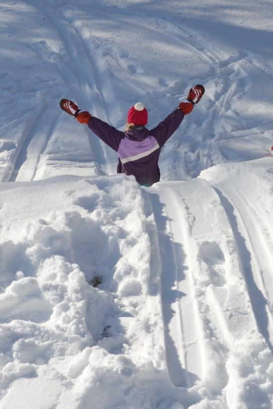 Enfant sur une luge dans un champs de neige